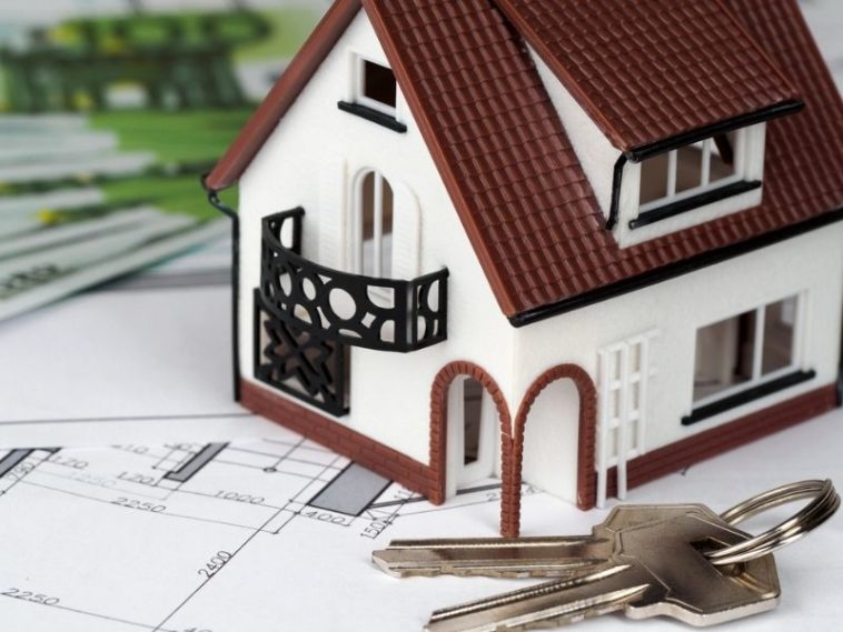House and keys on building plan with money on background